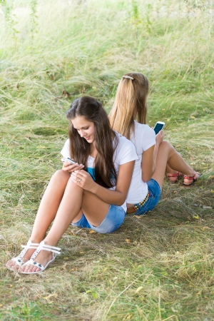 13 14 years: Two teenage girls with cell phones are sitting on the grass
