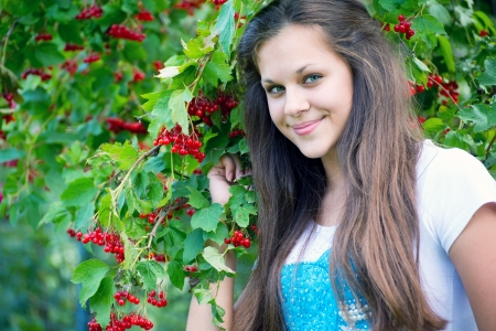 13 14 years: Teen girl near the red viburnum Stock Photo