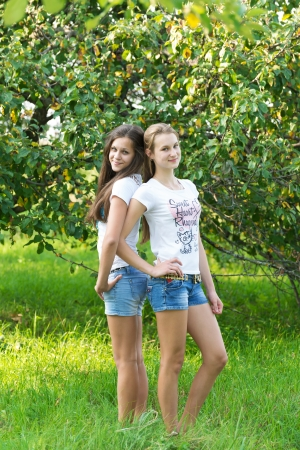 Girls in an apple orchard in summer photo