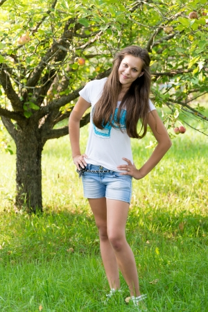 Girl in apple orchard in summer photo