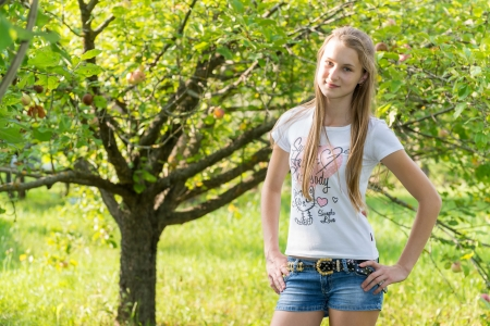 13 14 years: Girl in apple orchard in summer