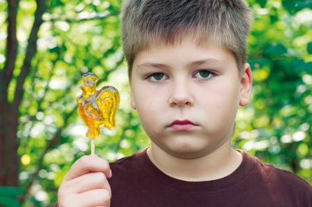 excess weight: Boy with lollipop in nature
