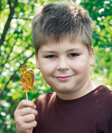 9 10 years: Boy with lollipop in nature