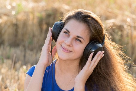 Girl listening to music in  field photo