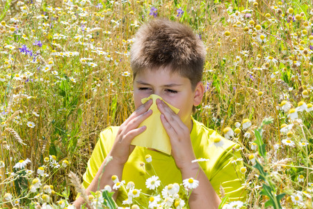 Boy with allergic rhinitis in the meadow