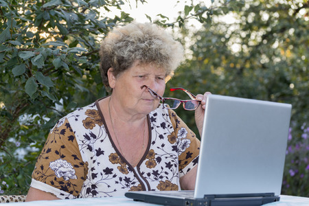 caucasion: elderly woman working on  a computer in the garden