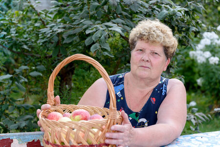 An elderly woman with a basket of apples in the garden
