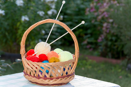 Wicker basket with knitting needles and a knitting photo