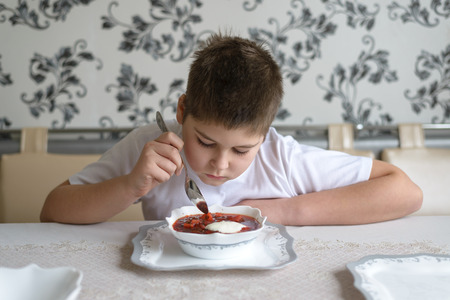 teenaged boys: Boy teenager eating soup at the kitchen table