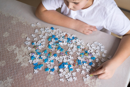 collects: Teenager boy collects puzzles at the table