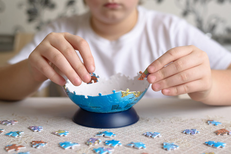 Teenager boy collects puzzles from  a Globe