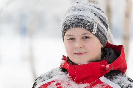 Teenager boy in winter park, birch grove in Russia photo