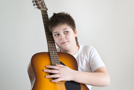 patio chair: Teenage Boy plays an acoustic guitar while relaxing on a patio chair.