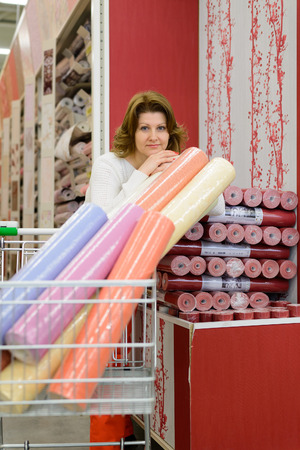 A Woman buys wallpaper in the store photo