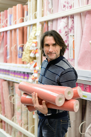 man holding a roll of a wallpaper in the store