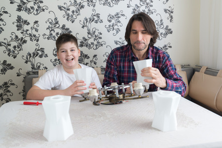 wall sconce: father and son are repairing the chandelier Stock Photo