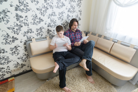 dad and son  with tablet computer indoors photo