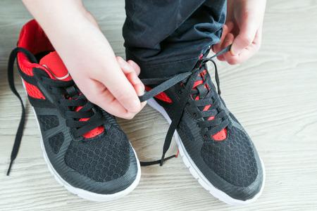 salud y deporte: El muchacho zapatos para correr es un cordones Foto de archivo