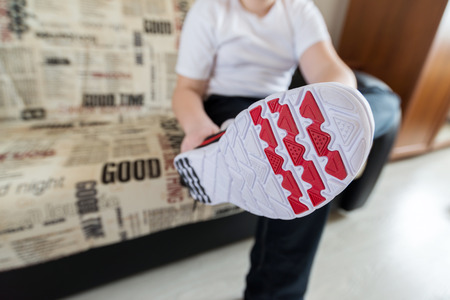 outsole: Teenager boy in running shoes in the living room