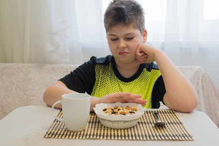 fullness: Teenager boy refuses to eat a oatmeal for breakfast