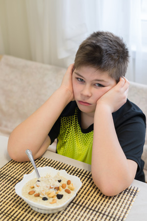 plenitude: Teenager boy refuses to eat a oatmeal for breakfast