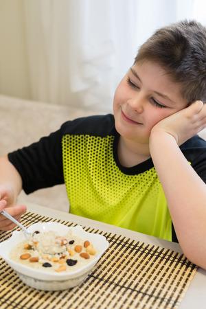 plenitude: Teenager boy has oatmeal for a  breakfast