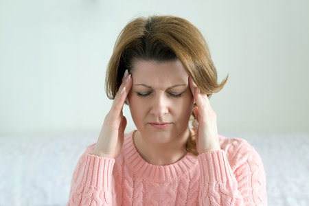 Woman holding hands on her head, depression, pain, migraine photo