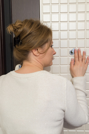 peephole: woman back looking to a peephole interior house hall Stock Photo