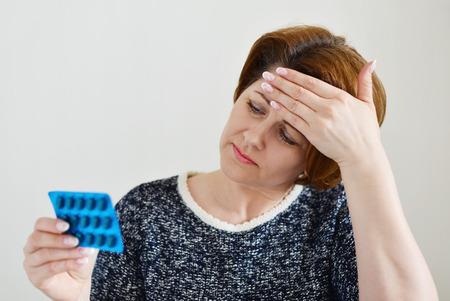 Adult woman taking a pill for a headache