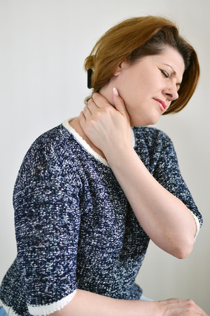 muscle spasm: Adult woman with neck pain on a light background