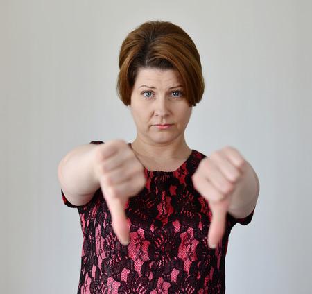 desprecio: Mujer joven enojado muestra su pulgar hacia abajo