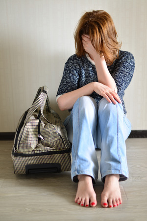 Sad woman sitting near the wall with a suitcase because divorce 写真素材