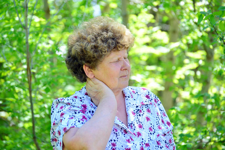 commercial tree care: Mature woman with a pain in the neck on the nature