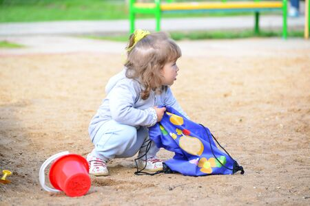 plastic scoop: A Little girl playing in the sandbox Stock Photo