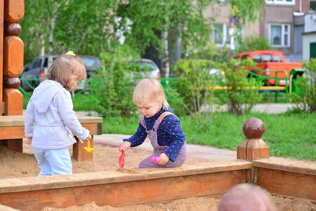 sandbox: Two little sisters playing in the sandbox Stock Photo