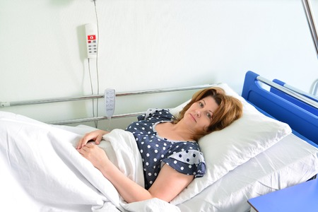 exam room: Female patient lying on a bed in hospital ward