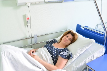 ward: Female patient lying on a bed in hospital ward
