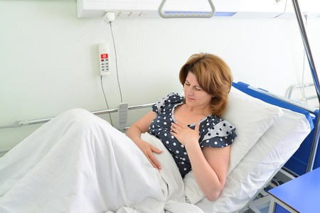 Female patient With heartfelt pain lying on a bed in hospital ward