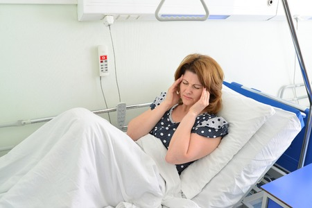 Female patient with headache on a bed in hospital ward