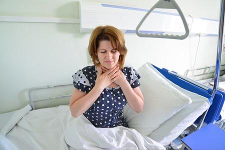 angina: Paciente femenino con angina de pecho en una cama en sala de hospital