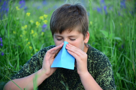 A teen boy with allergies in flowering herbs