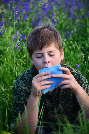 antihistamine: A teen boy with allergies in flowering herbs