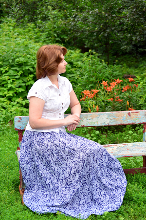 garth: An adult woman sitting on a bench in the garden Stock Photo