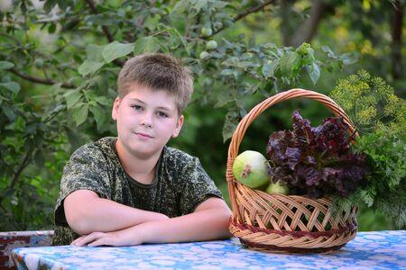 garden stuff: Teen Boy with a basket of fresh vegetables in the garden Stock Photo