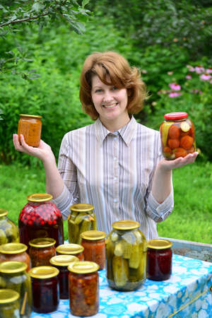 jams: Housewife with homemade pickles and jams in the garden
