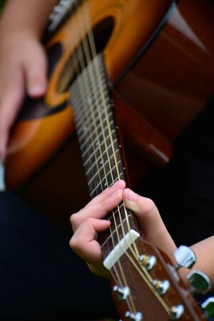 resonator: Detail of a guitar with a children hands Stock Photo