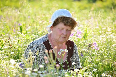 pensionary: An elderly woman on the  meadow in summer day Stock Photo