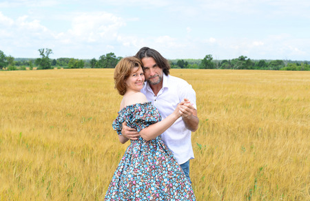 loving couples: Loving middle-aged couple standing in a field in summer