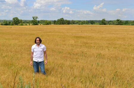 the stands: A man stands on the rye field
