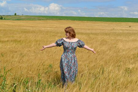 maxi dress: woman in maxi dress standing on the rye field